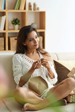 Image of a lady crocheting at home