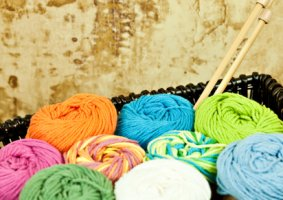Image of a Yarn Stash in a woven basket with knitting needles