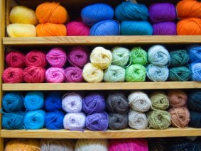 Image of shelves laden with colourful knitting yarns